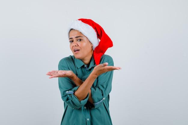 Молодая женщина показывает беспомощный жест в рубашке, шляпе санты и выглядит нерешительно, вид спереди.