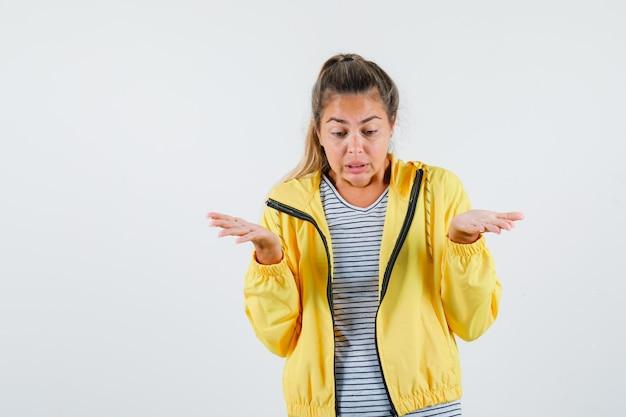 Tシャツ、ジャケットで無力なジェスチャーを示し、混乱しているように見える若い女性、正面図。
