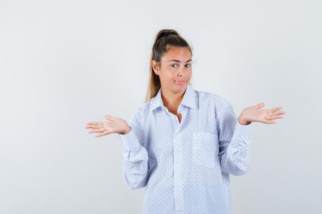 Молодая женщина демонстрирует беспомощный жест в белой рубашке и выглядит озадаченно