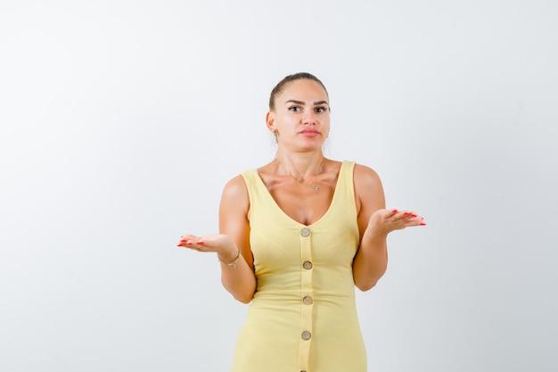 黄色のドレスで無力なジェスチャーを示し、混乱しているように見える若い女性。正面図。