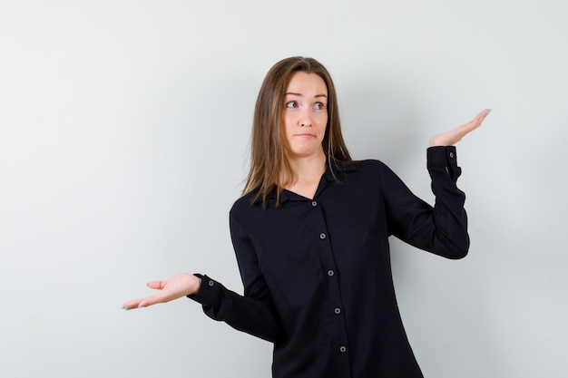 Giovane donna che mostra gesto impotente e sembra perplessa