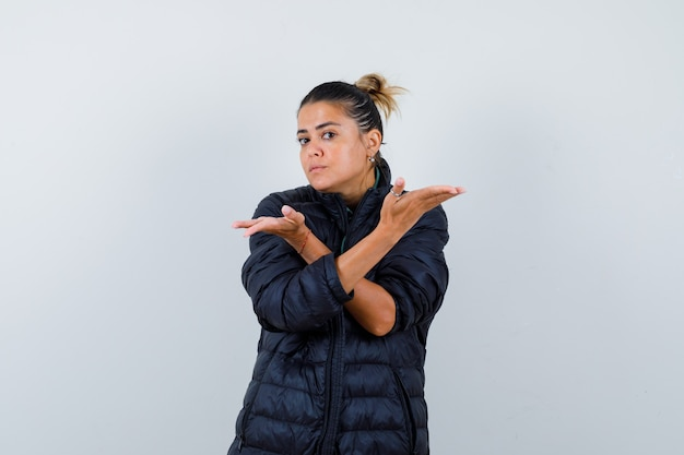 Young woman showing helpless gesture in puffer jacket and looking confused. front view.