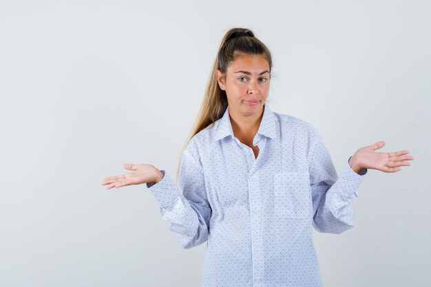 Young woman showing helpless gesture in white shirt and looking puzzled