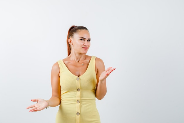 Young woman showing helpless gesture in yellow dress and looking puzzle