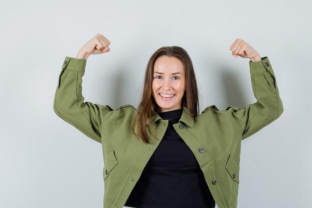녹색 재킷에 그녀의 팔 근육을 표시하고 강력한 전면보기를 찾고 젊은 여자.