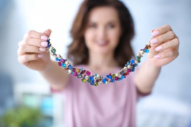 Молодая женщина показывает свое красивое ожерелье в помещении