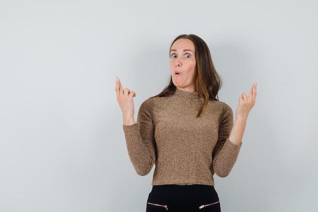 Giovane donna che mostra le sue dita incrociate in camicetta dorata e sembra strano