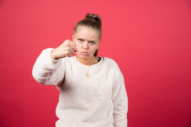 赤い壁に拳を見せている若い女性