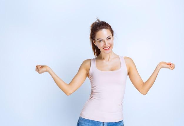 Молодая женщина показывает кулаки и чувствует себя счастливой