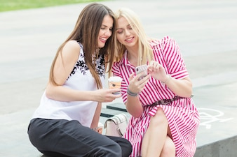 Young woman showing her mobile to her friend holding disposable coffee cup