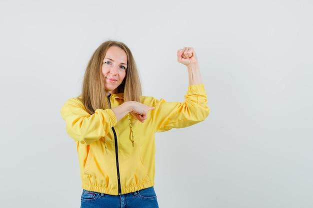 젊은 여자는 그녀의 근육을 보여주는 노란색 폭격기 재킷과 블루 진에 그것을 가리키고 강력한 찾고 있습니다. 전면보기.
