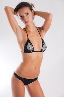 Young woman showing her perfect body in sexy black underwear on a white background