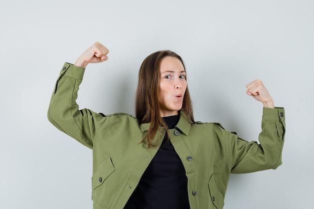 Giovane donna che mostra il suo potere in giacca verde, camicia nera e guardando abile, vista frontale.
