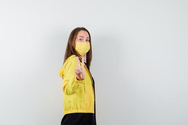 微細なジェスチャーでホールドを示す若い女性