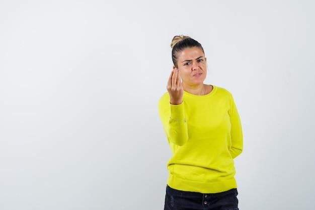 노란색 스웨터와 검은색 바지를 입은 이탈리아 제스처를 보여주고 감동을 주는 젊은 여성