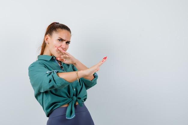 緑のシャツで空手チョップジェスチャーを示し、力強く見える若い女性。正面図。