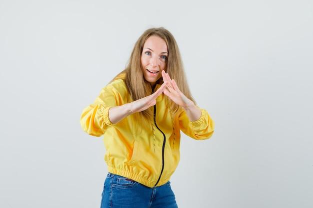 Молодая женщина показывает жест страхования жизни в желтой куртке бомбардировщика и голубых джинсах и выглядит оптимистично. передний план.