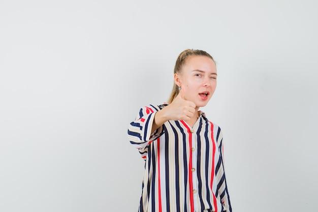 Молодая женщина показывает как жест и мигает в полосатой блузке и выглядит счастливой