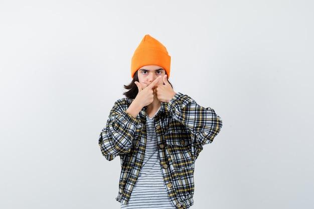 Giovane donna che mostra il gesto del perdente con un cappello arancione che sembra serio