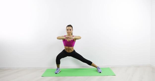 ジムで体操をしている若い女性美しい体の健康的なライフスタイル