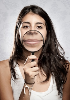 Young woman showing mouth through magnifying glass