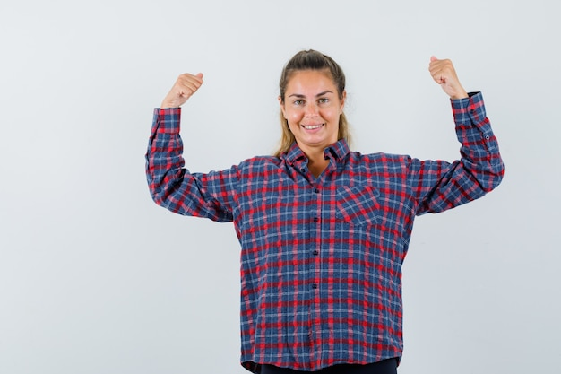 Giovane donna che mostra i muscoli in camicia controllata e che sembra potente