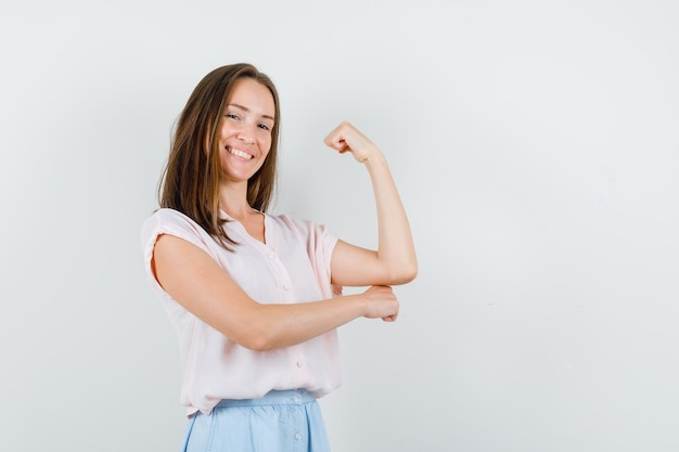 Молодая женщина показывает мышцы руки в футболке, юбке и выглядит веселой. передний план.