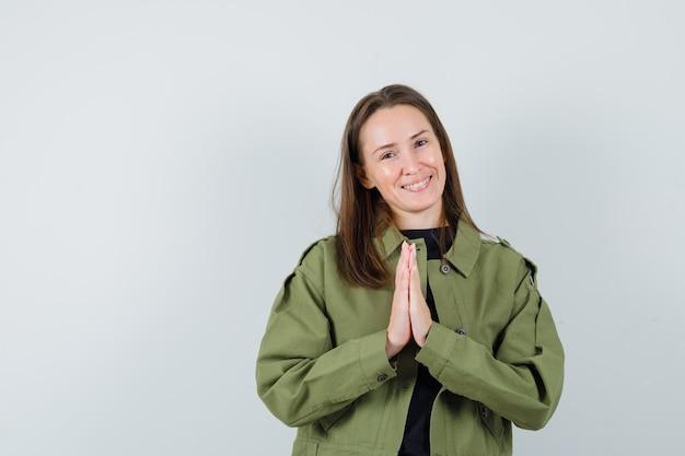 Giovane donna che mostra il gesto di namaste in giacca verde e sembra felice. vista frontale.