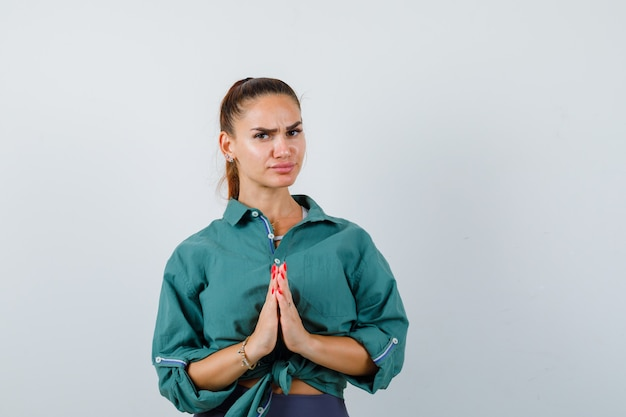 Молодая женщина показывает жест намасте в зеленой рубашке и смотрит вдумчивый, вид спереди.