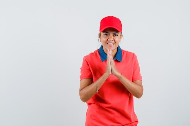 赤いシャツと帽子でナマステのジェスチャーを示し、きれいに見える若い女性。正面図。