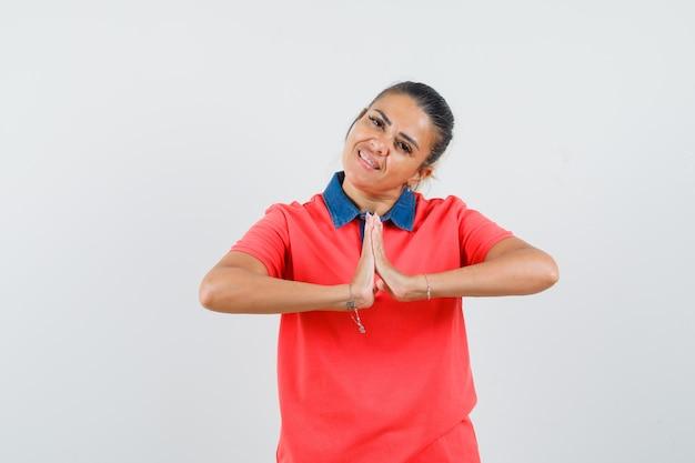 赤いtシャツでナマステのジェスチャーを示し、きれいに見える若い女性、正面図。