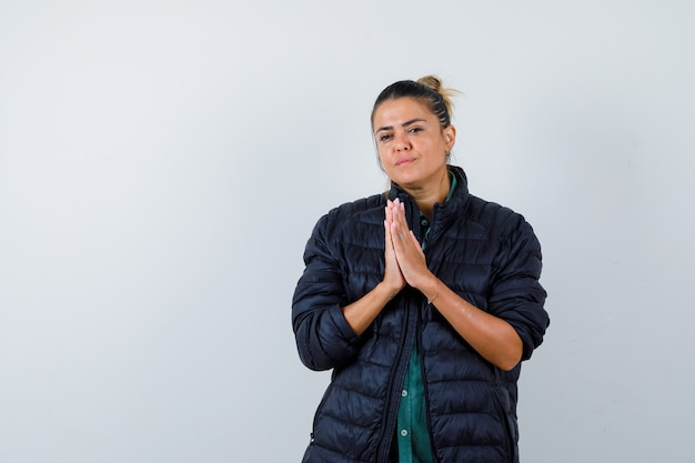 Young woman showing namaste gesture in puffer jacket and looking pensive. front view.