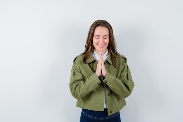 Giovane donna che mostra gesto di namaste in camicia, giacca e sembra felice, vista frontale.