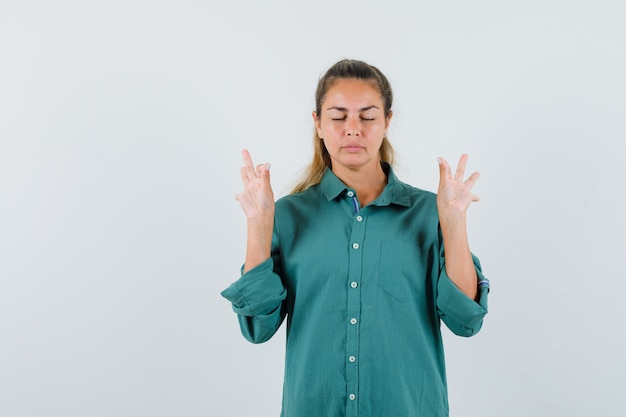 Young woman showing ok gesture in blue shirt and looking calm