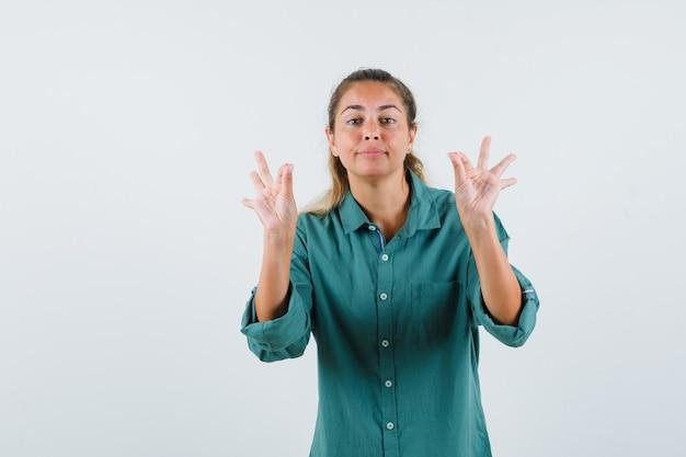 Giovane donna che mostra il gesto giusto in camicia blu e che sembra soddisfatta