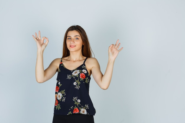 Young woman showing ok gesture in floral top and looking distrustful