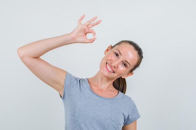 灰色のtシャツでokジェスチャーを示し、嬉しそうに見える若い女性、正面図。