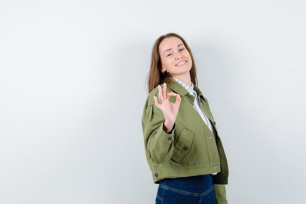 シャツ、ジャケットで大丈夫なジェスチャーを示し、自信を持って見える若い女性。正面図。