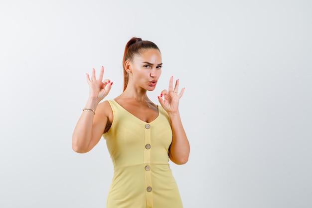 Молодая женщина показывает жест в желтом платье и выглядит уверенно