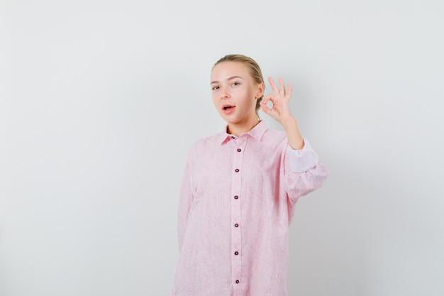 Giovane donna che mostra il gesto giusto in camicia rosa e che sembra soddisfatta
