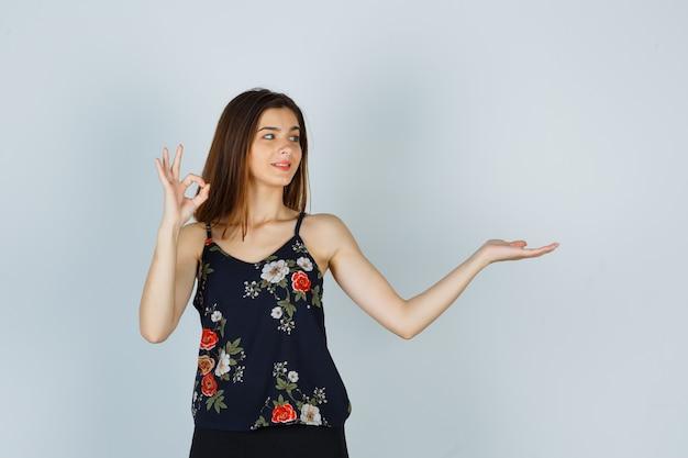 大丈夫なジェスチャーを示し、花のトップに手のひらを広げ、満足しているように見える若い女性
