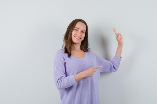 ライラックのブラウスで脇を指して幸せそうに見える間、大丈夫なジェスチャーを示す若い女性