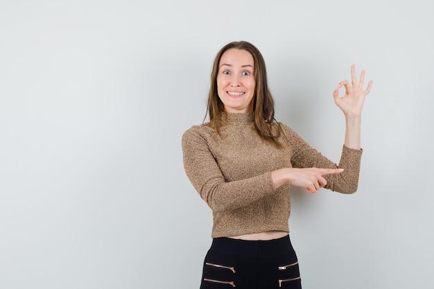 Молодая женщина показывает знак ок и указывает вправо в позолоченном золотом свитере и черных штанах и выглядит счастливой, вид спереди.