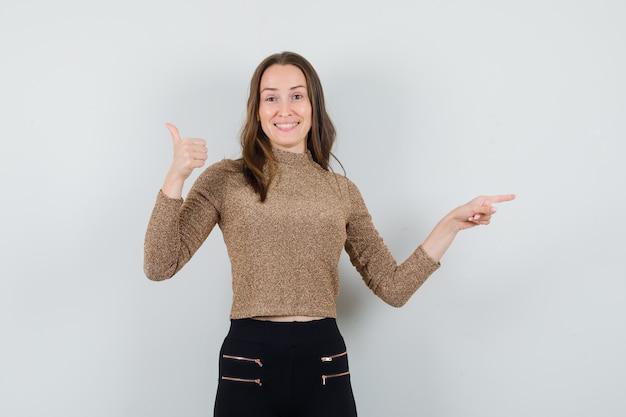Молодая женщина показывает знак ок и указывает вправо указательным пальцем в позолоченном золотом свитере и черных штанах и выглядит счастливой, вид спереди.
