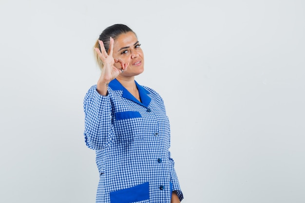 Young woman showing ok sign in blue gingham pajama shirt and looking pretty , front view.