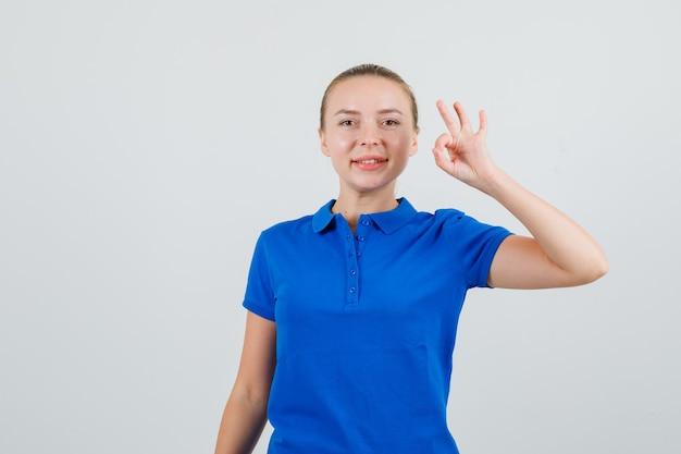 Giovane donna che mostra segno giusto in maglietta blu e sembra soddisfatta