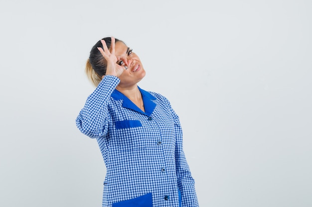 Young woman showing ok sign on eye in blue gingham pajama shirt and looking happy , front view.