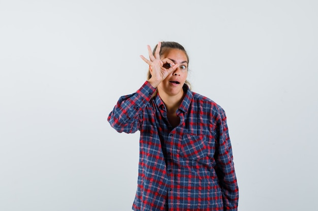 Young woman showing ok sign on eye in checked shirt and looking happy