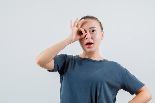 Giovane donna che mostra segno giusto sull'occhio in maglietta grigia e guardando stupito