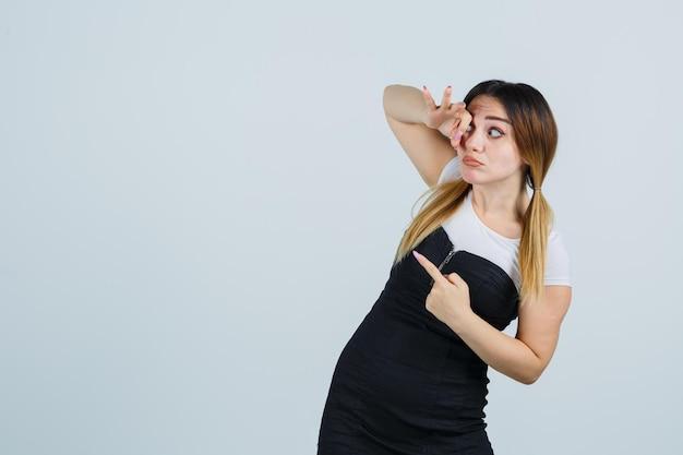 Giovane donna che mostra segno ok sull'occhio mentre indica a sinistra
